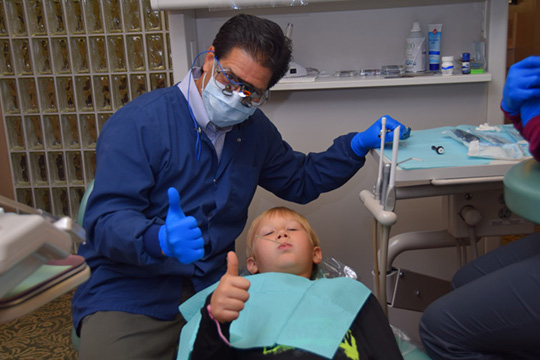 Dr. Lloyd and smiling kid in dental chair