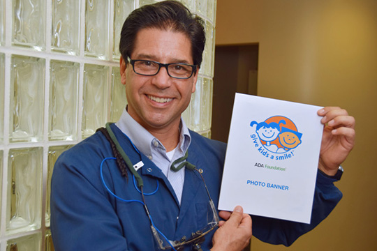 Dr. Lloyd holding a Give Kids a Smile flyer