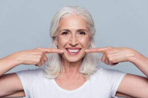 Older woman pointing to the cosmetic benefits of dental implants in Daytona Beach.