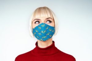 Woman wearing mask, concerned about gum disease and COVID-19